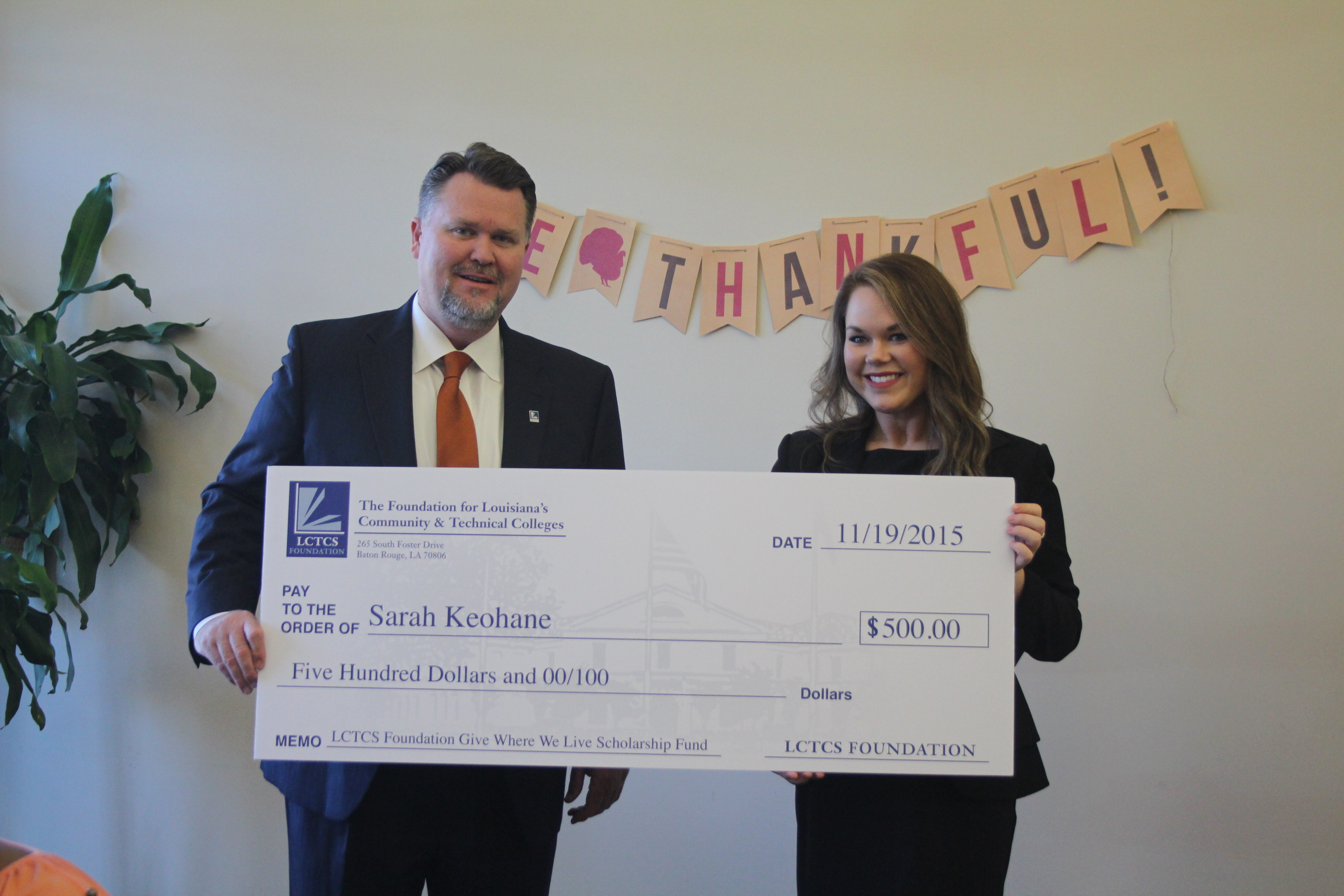 Sarah Keohane accepting a check for the Give Where We Live Scholarship Fund