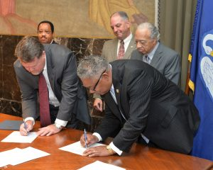 Dr. Sullivan and Dr. Ray L. Belton signing papers